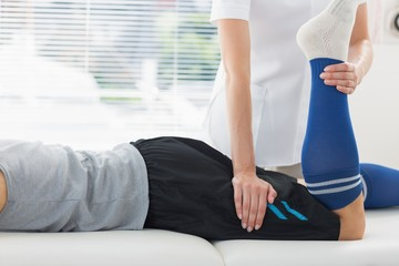 Physiotherapist working on leg of man