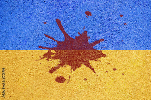 Ukraine flag painted on old concrete wall with blood blot