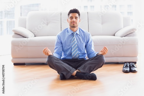 Businessman meditating in lotus pose on the floor