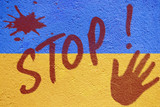 Ukraine flag painted on old concrete wall with STOP inscription