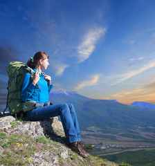 Woman with backpack enjoying sunset on top of mountain