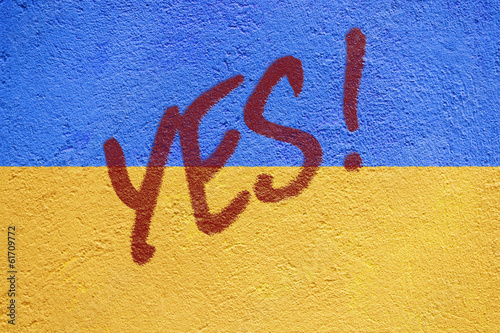 Ukraine flag painted on old concrete wall with YES inscription