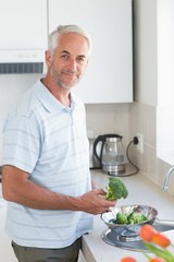 Casual man rinsing broccoli in colander and smiling at camera