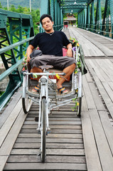 Thai Man sit at Riding tricycle on Bridge over Pai River