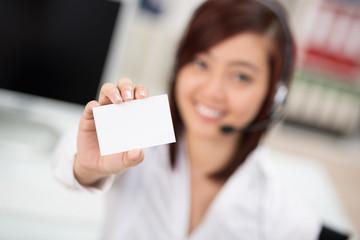 lächelnde frau im büro zeigt weiße karte