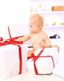 Adorable baby girl with gift boxes posing