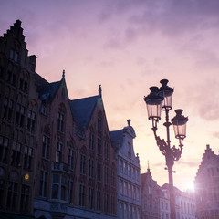 Silhouettes of city center houses in Bruges against beautiful su