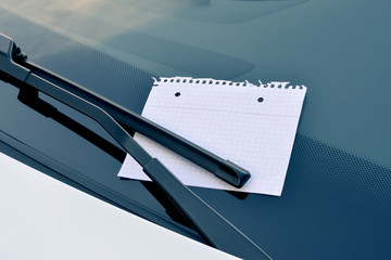 sheet of paper under a windshield wiper