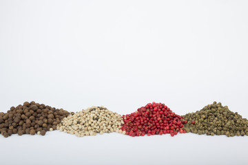 Black, white, red and green peppercorns on white background