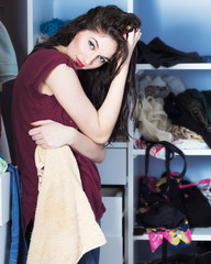 Beautiful girl in a woman's wardrobe with a towel on his arm