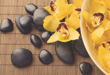 massage stones with orchid flowers on mat