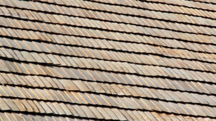 The brown wooden shingle shake roof of a big house