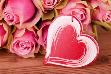 pink roses and red heart on wooden table