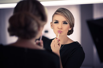 young beautiful woman does a house make up