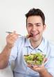 Lachender junger Mann isst einen gemischten Salat