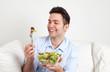 Lachender junger Mann freut sich über seinen Salat