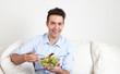 Junger Mann isst frischen Salat auf dem Sofa