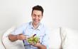 Junger Mann auf dem Sofa freut sich über seinen Salat