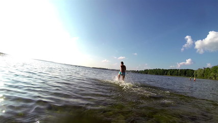 Running towards the lake on a swimsuit