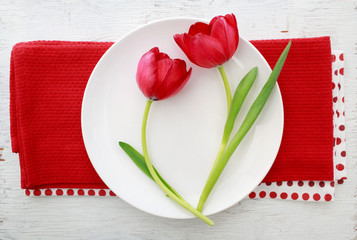 Red tulips on white plate