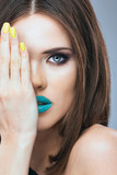 Young beauty model , blue lips, yellow nails. Close up