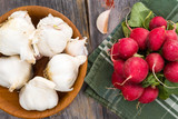 Whole bulbs of fresh garlic with fresh radishes