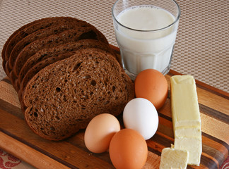 Bread, Butter, Eggs, Milk on a Cutting Board