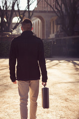 Handsome young man walking alone with suitcase