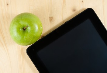 top of view of digital tablet pc and green apple on wood table
