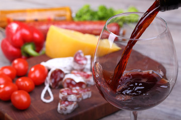 Pouring wine into glass and food background