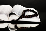 Russian bible and wooden rosary on black background