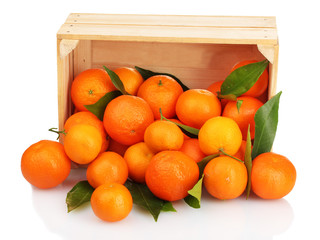 Ripe tasty tangerines with leaves in wooden box dropped