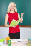 School teacher near table on blackboard background