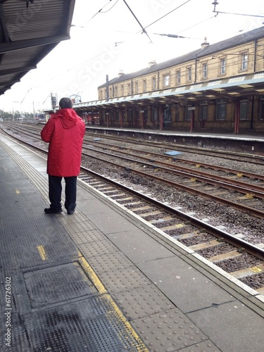 Man in red jacket waiting at a train station platform