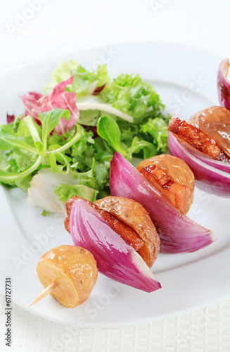 Bacon and potato skewer with salad greens
