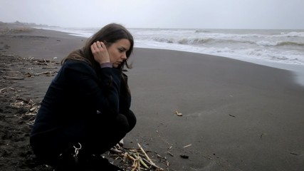 Woman sitting on the beach feeling abandoned