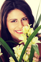 Beautiful young woman smelling orchid flower