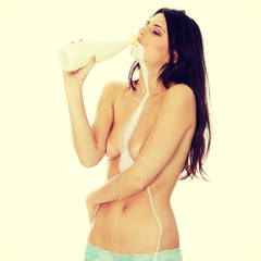 Young topless woman drinking milk from bottle. Isolated on white