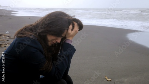 Sad desperate woman crying on the beach during storm