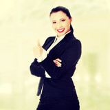 Confident business woman standing and gesturing ok