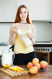 ordinary woman cooking milkshake with mango