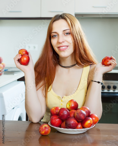 Happy pretty  woman holding nectarines