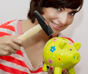 Young woman breaks a porcelain piggy bank with a hammer