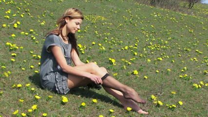 Woman putting on black stockings in a field