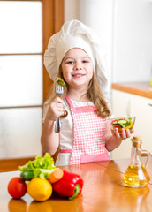 Chef girl preparing and tasting healthy food over white backgrou