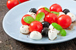 Fresh salad with cherry tomatoes, basil, mozzarella and olives