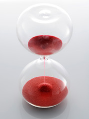 Clear glass hourglass with red sand