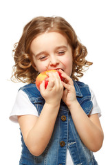 Little girl in a denim jacket holding a red apple. Isolated on w