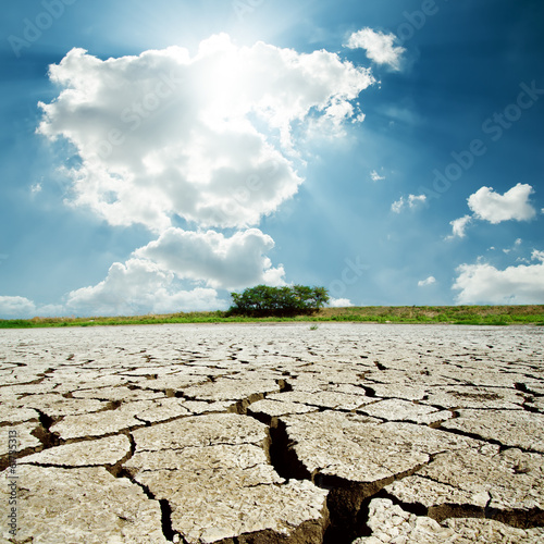 Leinwanddruck Bild drought earth and sun in cloudy sky