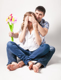 man closing eyes of pregnant wife and giving her flower